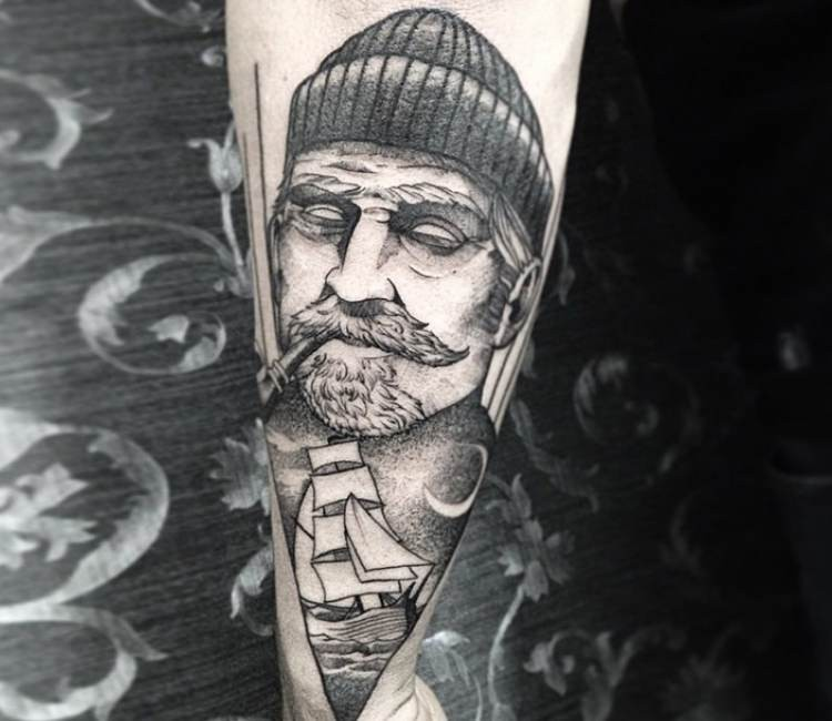 Cool looking black and white style old sailor with ship tattoo on forearm
