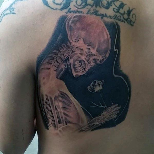 Cool looking X-Ray like human skeleton tattoo on back with small flower