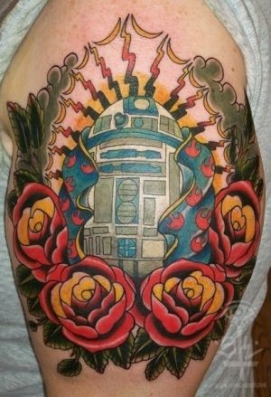 Cool multicolored old school R2D2 droid tattoo on shoulder stylized with flowers