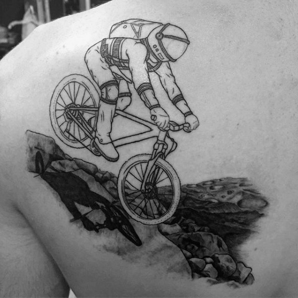Cool painted black ink astronaut on bicycle space planet tattoo on shoulder