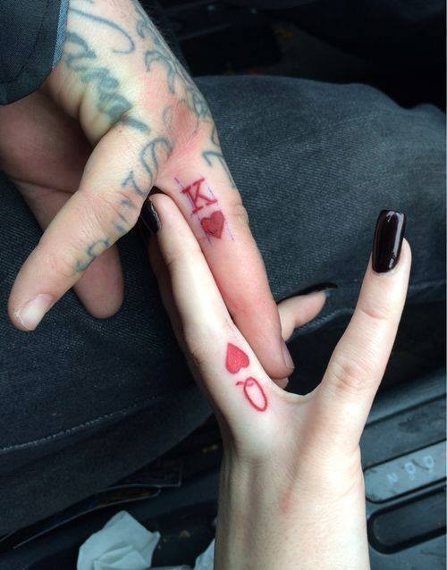 Cool red colored homemade couple tattoo on fingers