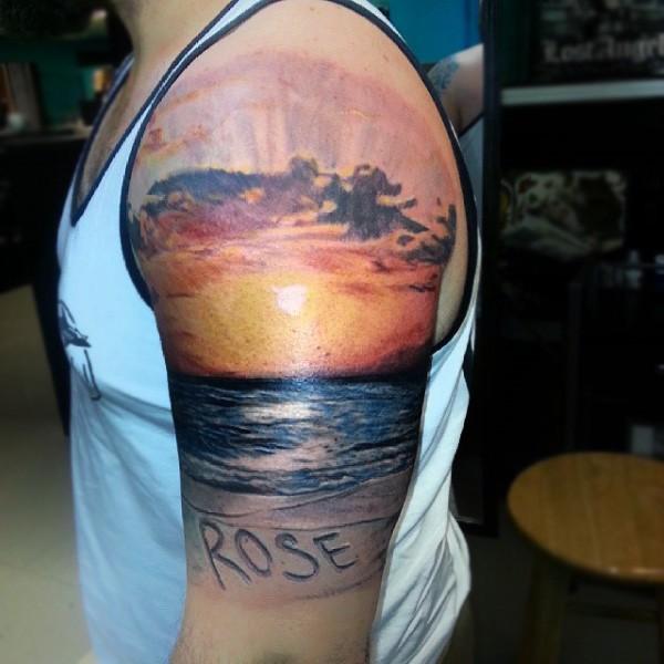 fresco multicolore oceano su tramonto e lettere tatuaggio su spalla