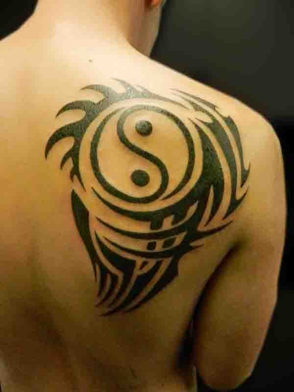 Cool sharp dark black ink Yin Yang special stylized symbol tattoo on man&quots shoulder blade with tribal elements