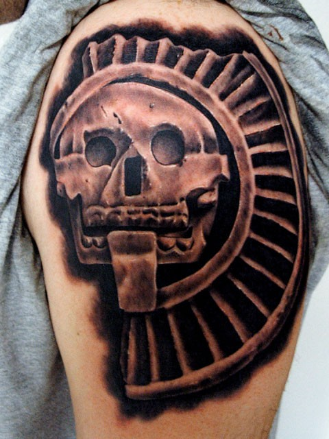 Cool stone skull deity tattoo on shoulder by goethe