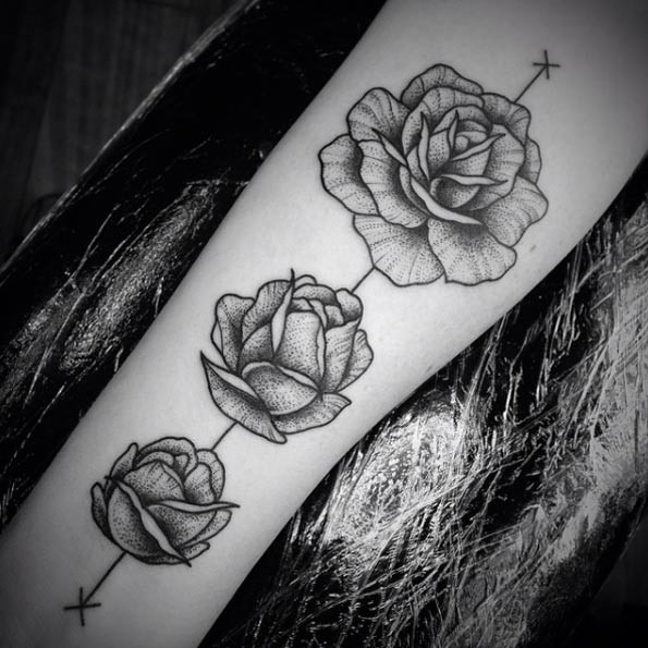 Cool various shaped black ink rose tattoo on forearm