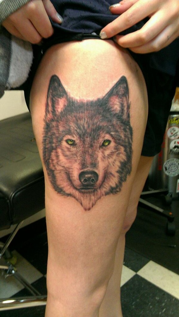 Cool wolf with yellow eyes tattoo on thigh