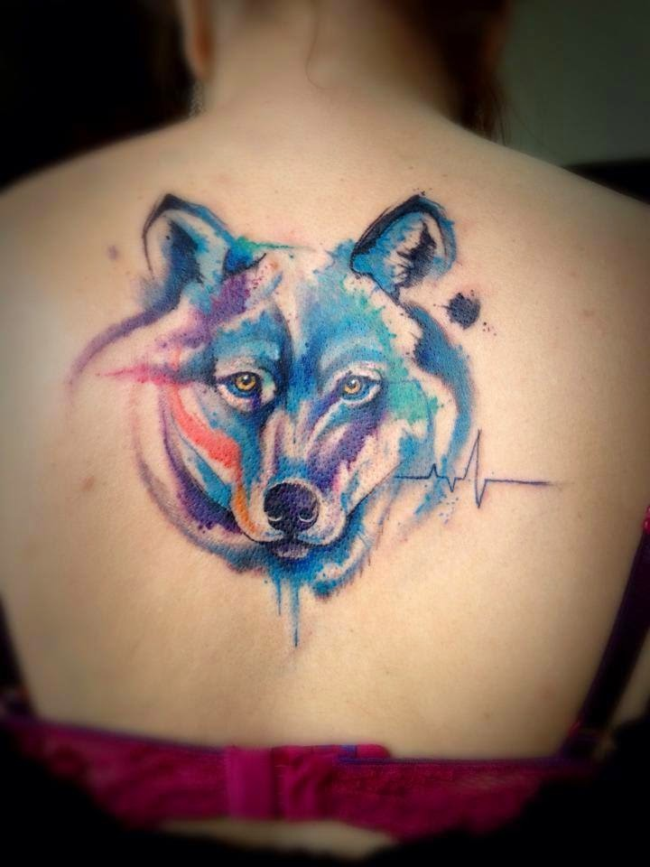 Cool wolf&quots head with colored paint drips tattoo on lady&quots back in watercolor style with heart rhythm