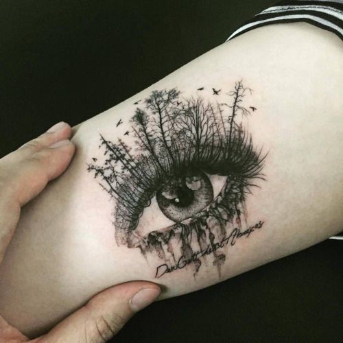 Creative painted beautiful looking tattoo of woman eye with trees and lettering