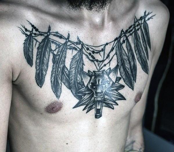 Tatuaje en el pecho,  collar con plumas y cabeza de dragón