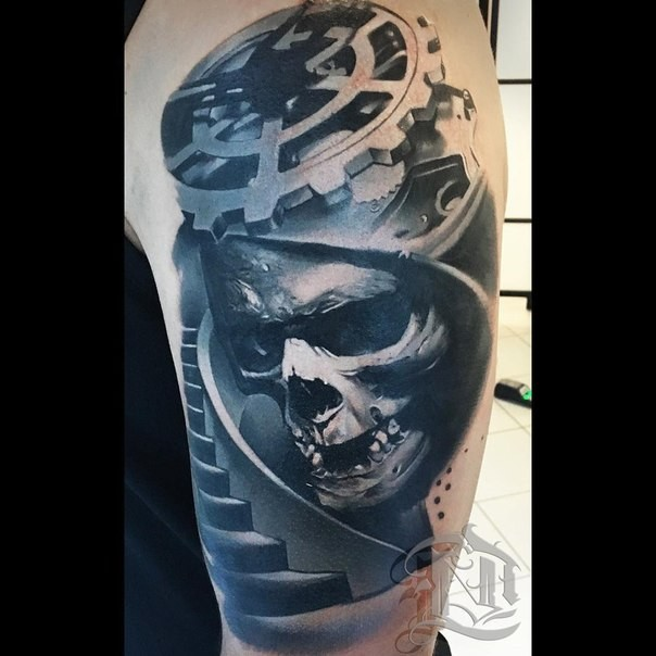 Creepy biomechanical style shoulder tattoo of human skull with big stairs