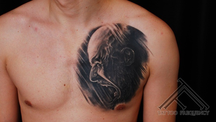 Creepy black ink screaming man tattoo on chest