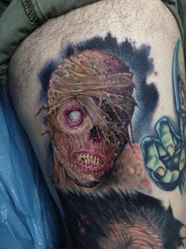 Creepy colored horror style thigh tattoo of monster face