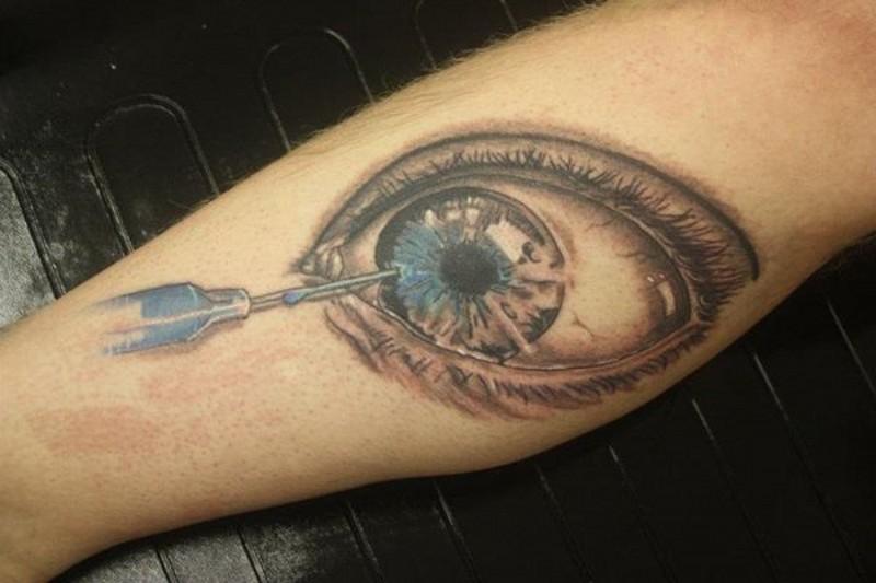 Creepy designed and painted big eye with needle tattoo on leg