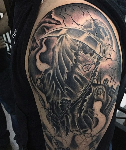 Creepy looking black and white Death skeleton tattoo on shoulder combined with dark cemetery