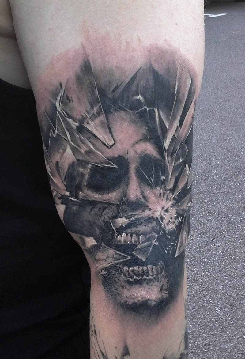 Creepy looking black ink shoulder tattoo of broken glass with monster face