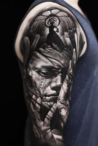 Creepy looking black ink shoulder tattoo of man monster face