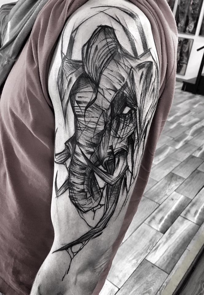 Creepy looking black ink upper arm tattoo of elephant by Inez Janiak