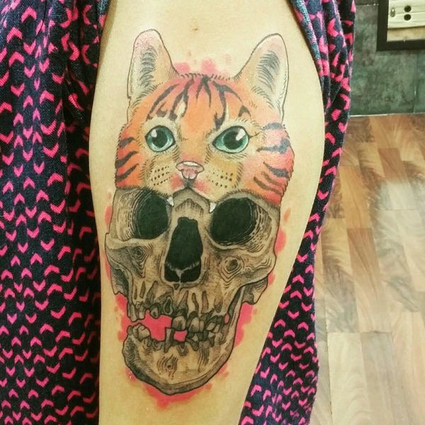 Creepy looking colored arm tattoo of human skull with cat shaped hat