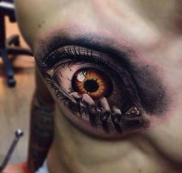 Creepy looking colored chest tattoo of human eye with hand