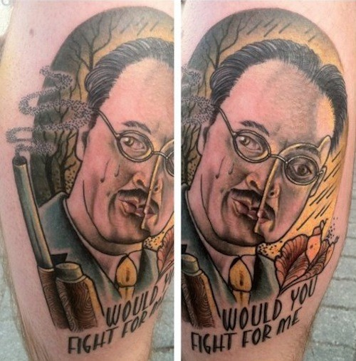 Creepy looking colored man portrait with lettering tattoo on leg