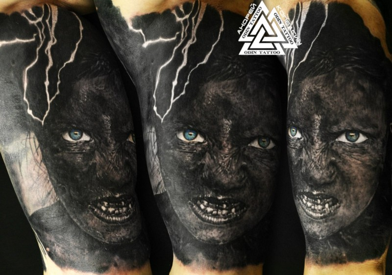 Creepy looking colored shoulder tattoo of monster creepy face