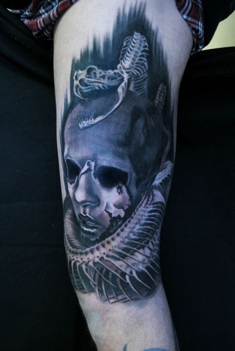 Creepy looking colored shoulder tattoo of monster clown with snake skeleton