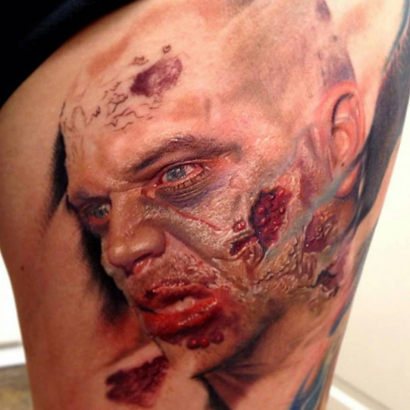 Creepy looking colored thigh tattoo of zombie man face