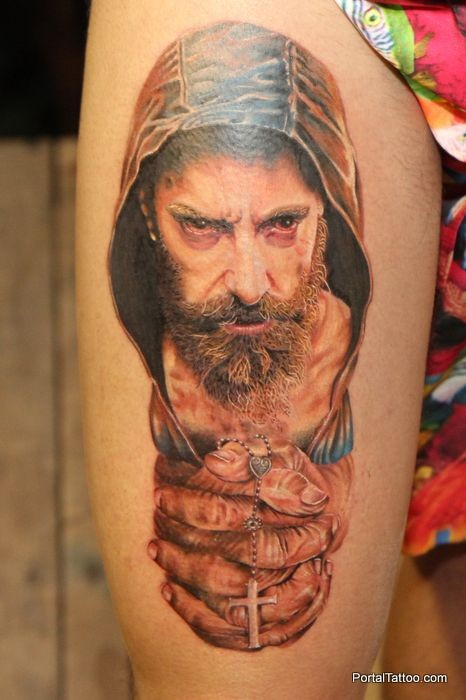 Creepy looking colored thigh tattoo of man with hood and cross