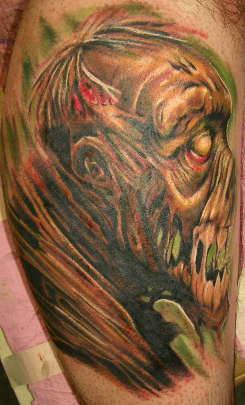Creepy painted and colored big monster face tattoo on arm
