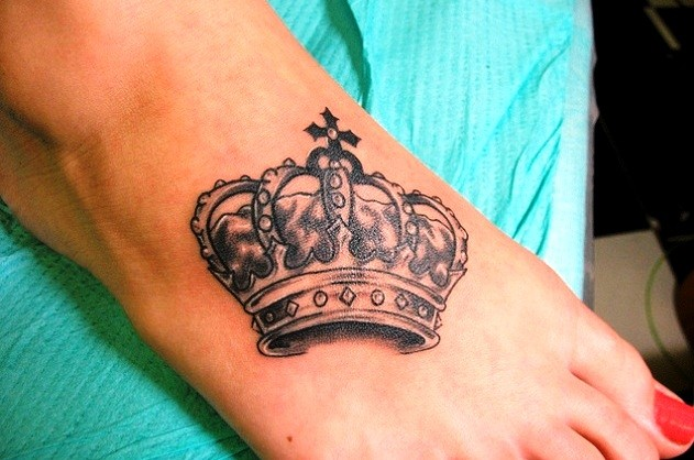 Crown tattoo on foot with lot of patterns