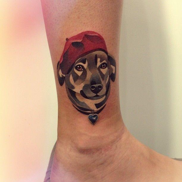 Tatuaggio bellissimo sulla gamba la testa del cane con berretto