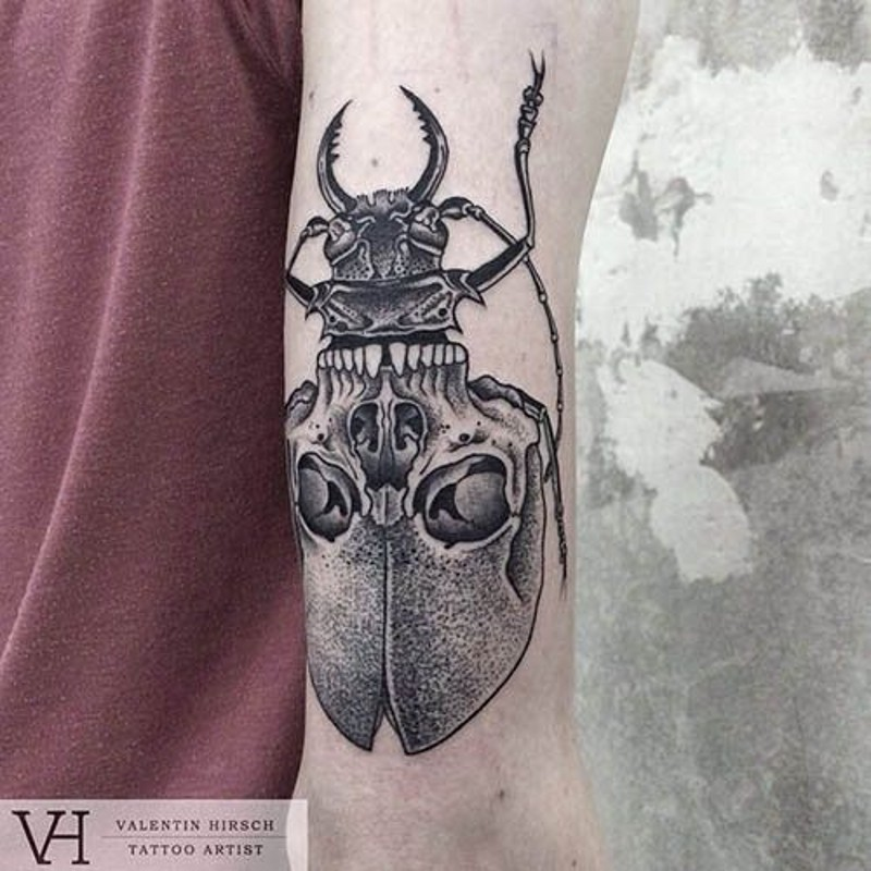 Cult like half skull half insect tattoo on arm