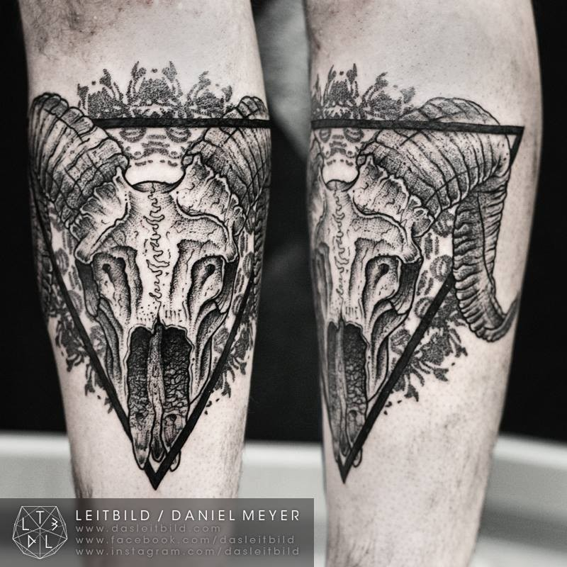 Cult style black ink forearm tattoo of animal skull with black triangle
