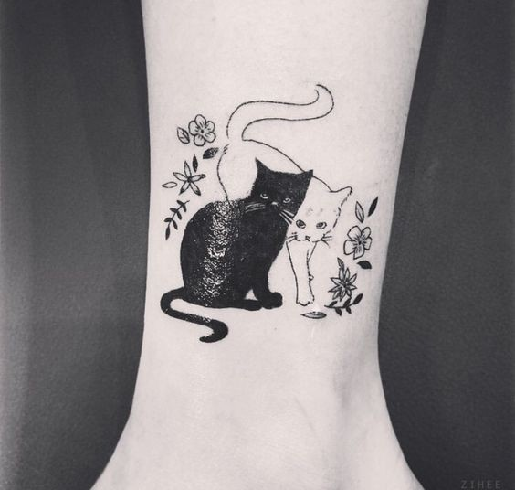 Cute black cat and white cat tattoo on ankle with tiny flowers