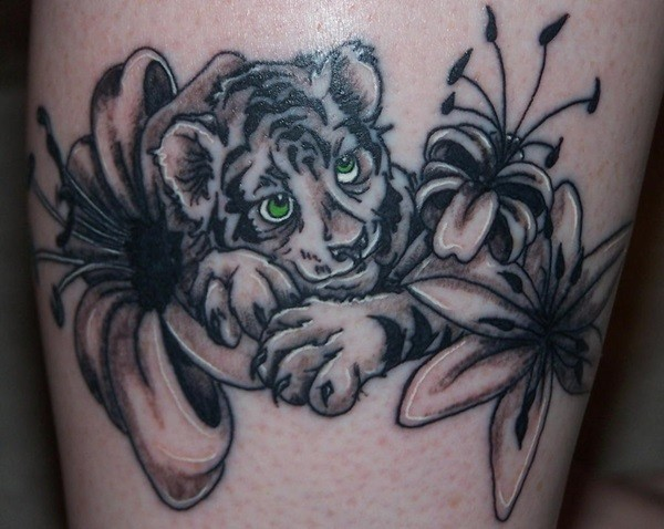 Cute cartoon like colored baby tiger tattoo combined with jungle flowers
