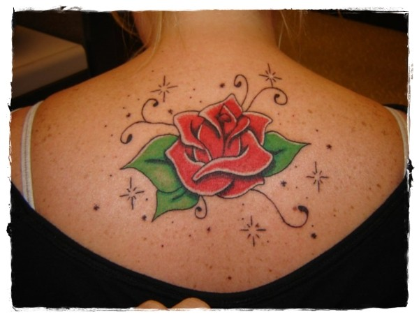 Cute cartoon style painted and colored rose tattoo on upper back