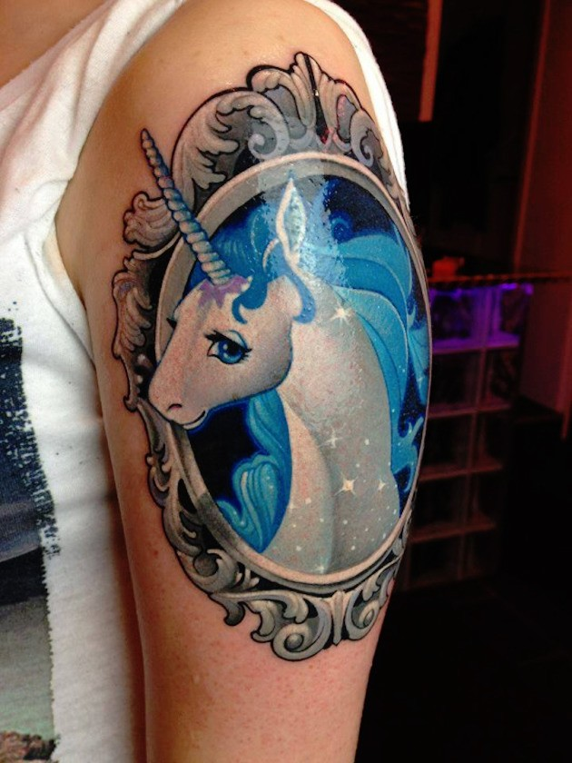 Cute cartoon unicorn in grotesque old frame colored shoulder tattoo with tiny sparkles
