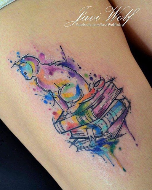 Cute cat sitting on pale of thick books rainbow colored thigh tattoo in watercolor style by Javi Wolf