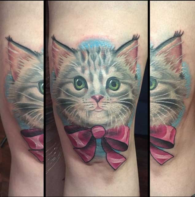 Cute colored kitten with pink ribbon bow tattoo