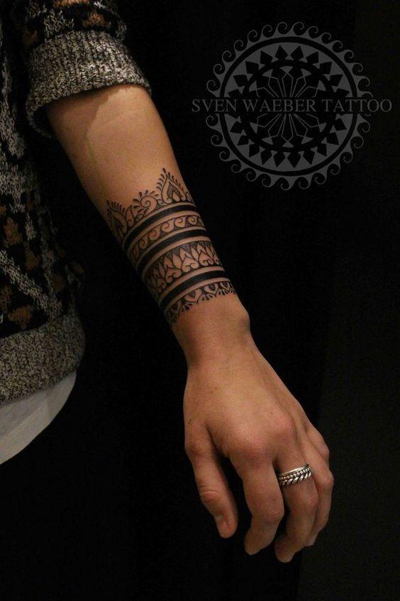 Simpatici ornamenti floreali in inchiostro nero tatuati sul braccio
