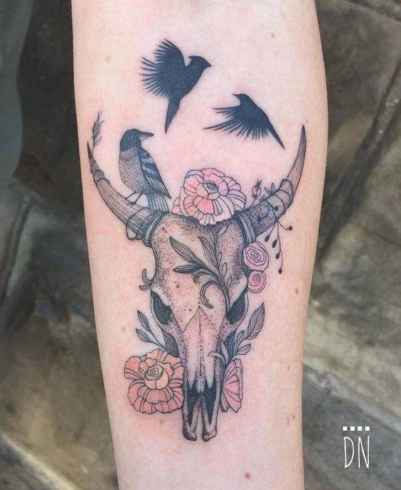 Simpatico stile illustrativo colorato tatuaggio dell&quotavambraccio di teschio animale con fiori e uccelli di Dino Nemec