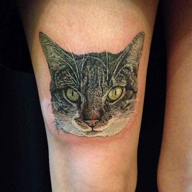 Cute lifelike colored thigh tattoo of big cat head