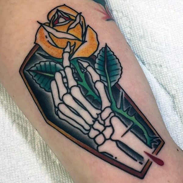Cute little coffin with skeleton hand and yellow rose tattoo on arm