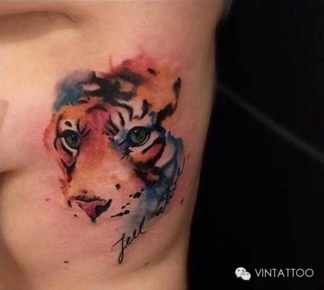 Cute looking colored side tattoo of tiger head with lettering