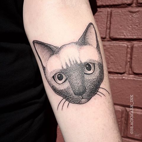Cute looking forearm tattoo of dot style cat portrait