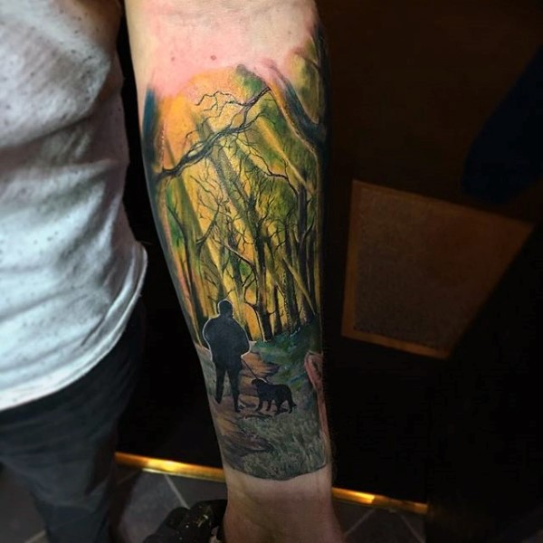 Cute multicolored man with dog in old forest tattoo on arm