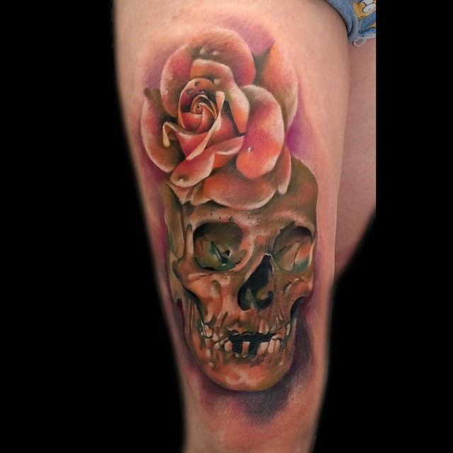 Cute painted and colored skull tattoo on thigh with detailed rose flower