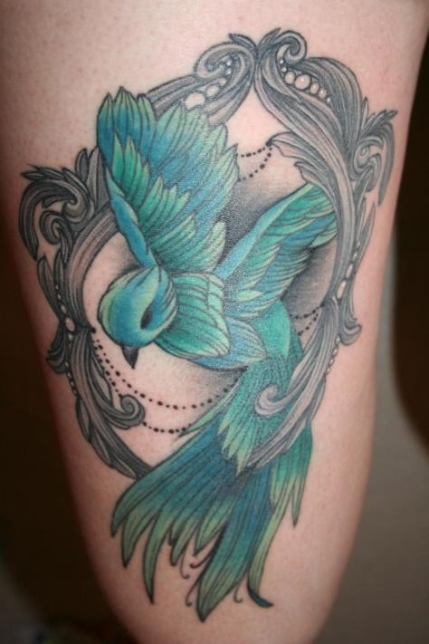 Cute painted little colored bird portrait tattoo on thigh