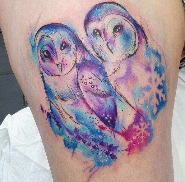 Cute pair of owls colored designed with snowdrops tattoo in watercolor style