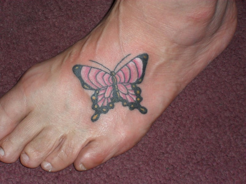 Cute pink with black butterfly foot tattoo